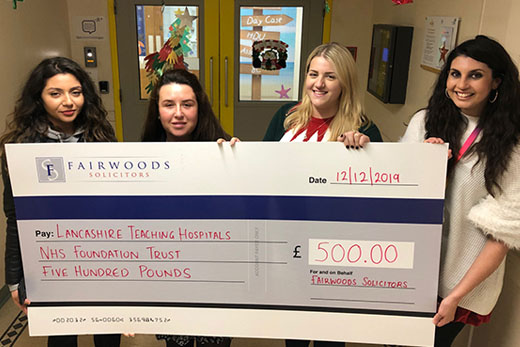 Four business women handing over a cheque to Lancashire Teaching Hospitals Charity